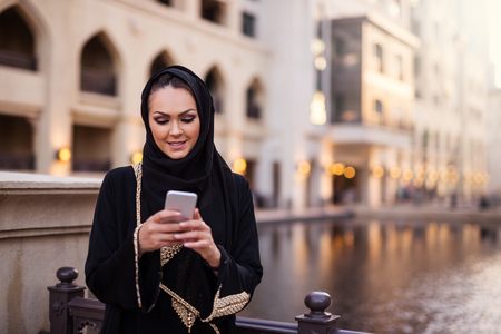 lady on phone: Pretty muslim lady using mobile phone outdoors.