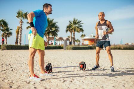 hombres haciendo ejercicio: Dos hombres ejercitan al aire libre en la playa.