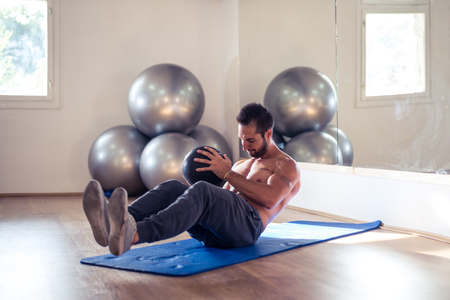 laying abs exercise: Sportsman training with an exercise ball. Stock Photo