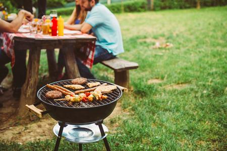 Vrienden genieten van barbecue tijd in de natuur.