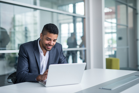 Afro-Amerikaanse zakenman werken op een laptop. Stockfoto