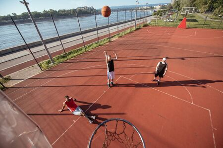 ouside: Team of basketball players playing basket outdoors. Stock Photo