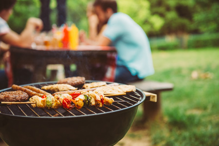 Friends making barbecue and having lunch in the nature. Archivio Fotografico