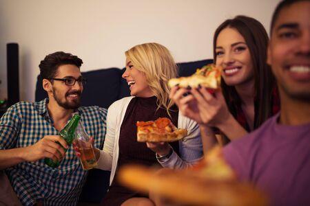 Vrienden die pizza thuis samen eten.