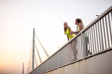 frienship: Two girls standing on the bridge and chatting together.