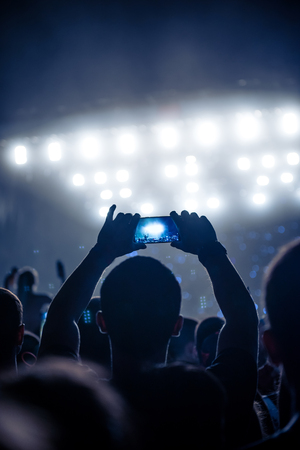 festival moments: Man capturing moments on a music festival. Stock Photo