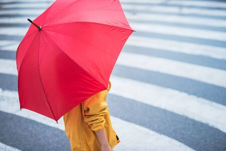 selective focus: Woman with umbrella crossing the pedestrian. Selective focus on the hand.