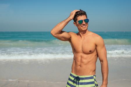 sin camisa: Apuesto hombre sonriente que disfruta de día en la playa. Foto de archivo