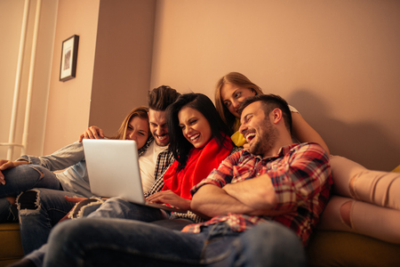tv show: Group of friends enjoying watching TV show together. Stock Photo