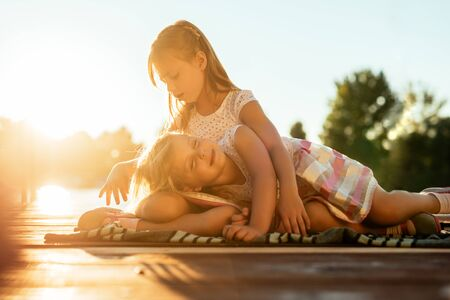 togther: Two beautiful sisters sharing tender moment outdoors. Stock Photo
