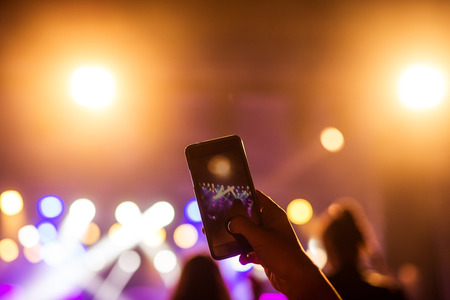 festival moments: Capturing best moments of the festival with mobile phone. Stock Photo