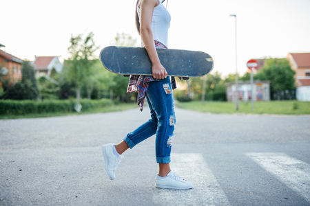 low angle: Low angle shot of a girl with a skate.