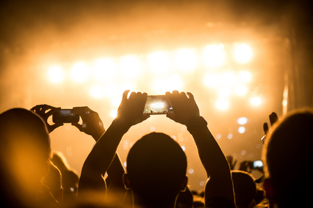 festival moments: Girl capturing best festival moments with mobile phone. Stock Photo