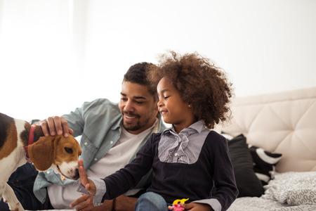アフリカ系アメリカ人の家族が、犬と遊ぶ。 写真素材