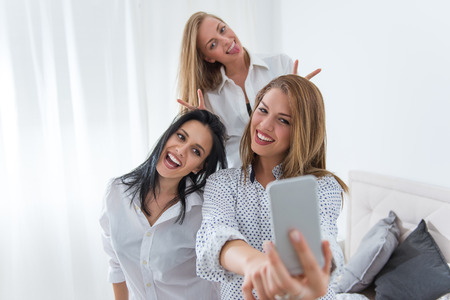 Beautiful girls making selfie together at home.