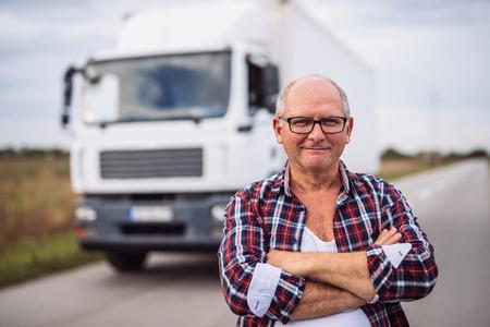 Portret van een vrachtwagenchauffeur met gekruiste wapens die zich voor de vrachtwagen bevinden.