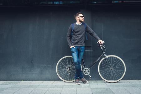 Een jonge stijlvolle hipster stellen naast zijn fiets. Stockfoto