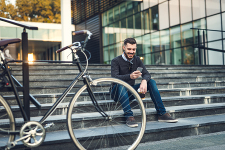 Handsome hipster browsing the net during a coffee break. Stock Photo