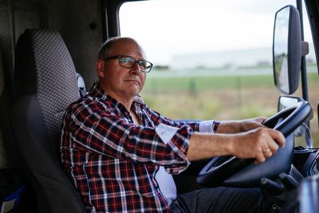 바퀴를 들고 수석 트럭 운전사의 초상화입니다. 스톡 콘텐츠