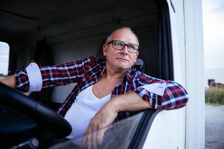 Portret van een hogere vrachtwagenchauffeur die een wiel houdt. Stockfoto