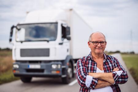 Portret van een hogere vrachtwagenchauffeur stellen naast zijn truck.