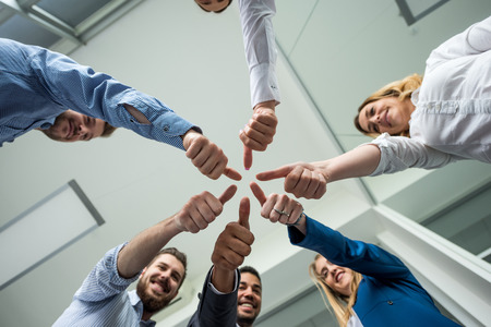 offiice: Businesspeople showing thumbs up in an offiice.
