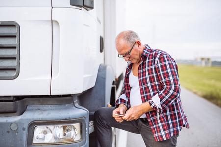 ciężarówka: Senior driver texting on a mobile phone next to truck outdoors.