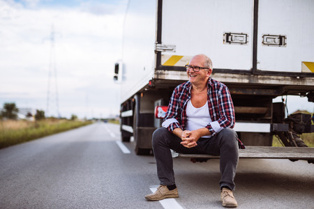 Senior truck driver posing next to his truck. Stock Photo
