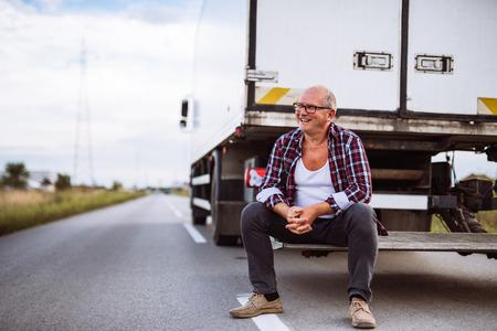 Starszy kierowca ciężarówki stwarzających obok jego samochodu.