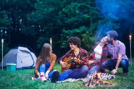 Happy friends listening to the music while camping at night.