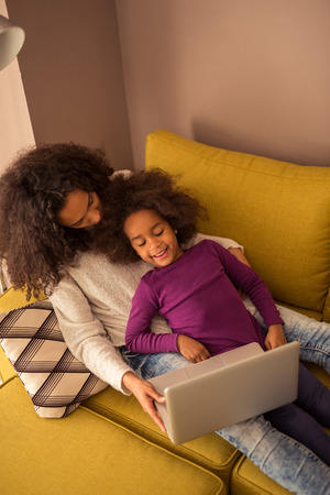 woman lying in bed: Cute african american girl watching cartoons with mom.