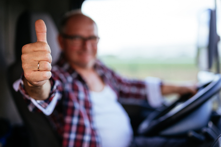 Senior man driving a truck and showing thumbs up.