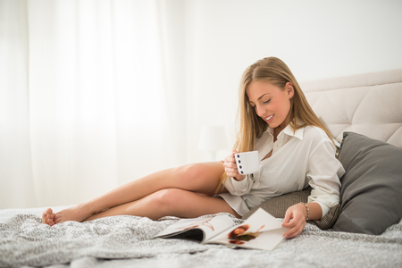 pj's: Beautiful girl reading a magazine and drinking coffee.
