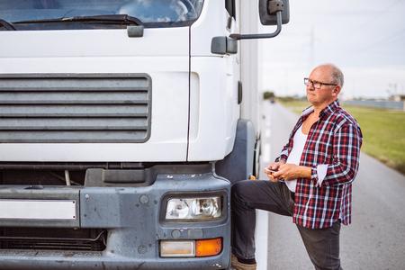 camionista maggiore che controlla il suo telefono cellulare.