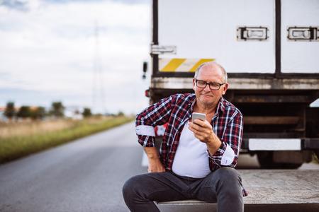 Senior vrachtwagenchauffeur controleren van zijn mobiele telefoon.