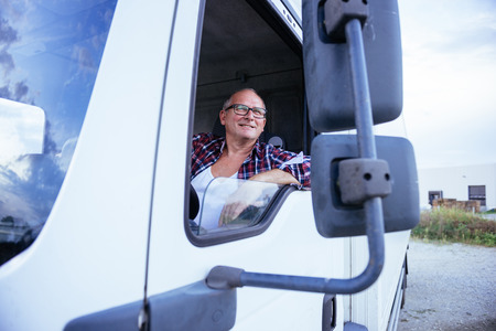 Senior man driving a truck and smiling.