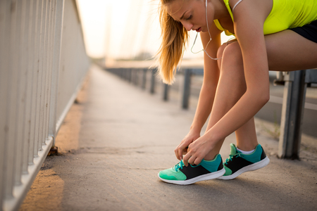 Attractive female tying a shoelace while running outdoors.