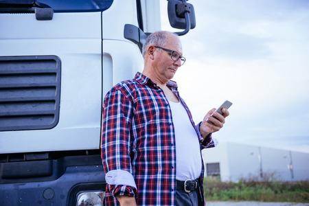 Senior trunk driver texting outdoors next to his trunk. Reklamní fotografie