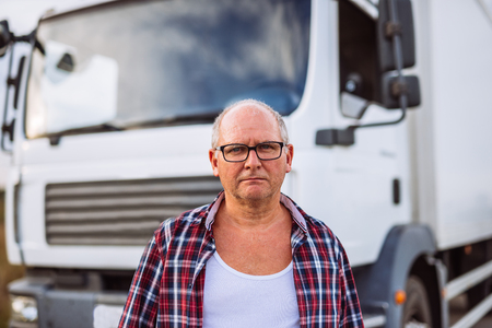 Portrait of a senior truck driver in front of his truck. Stock Photo