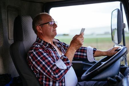 Senior man het besturen van een vrachtwagen en texting op een mobiele telefoon. Stockfoto