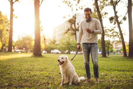 야외에서 문자 메시지 동안 그의 개를 산책하는 잘 생긴 남자.