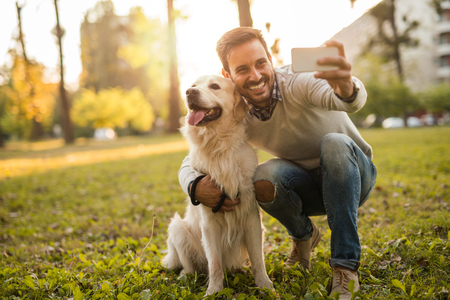 Man making a selfie with his golden retriever outdoors.