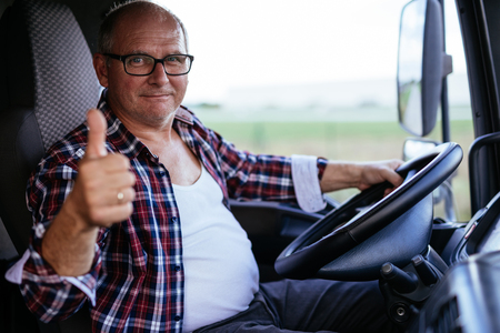 Senior truck driver showing thumbs up while driving. Stockfoto