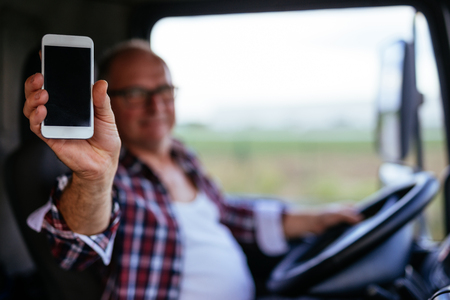 hand truck: Senior truck driver showing mobile phone while driving.