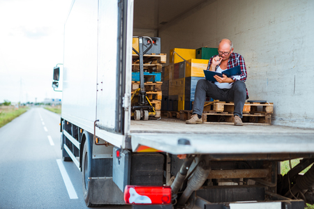 Senior driver reading a document while sitting in a truck.
