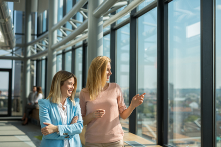 sucessful: Two business woman looking through the office window. Stock Photo