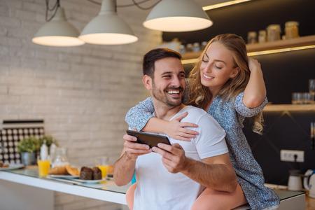 Paar die een digitale tablet gebruiken terwijl thuis het hebben van ontbijt.