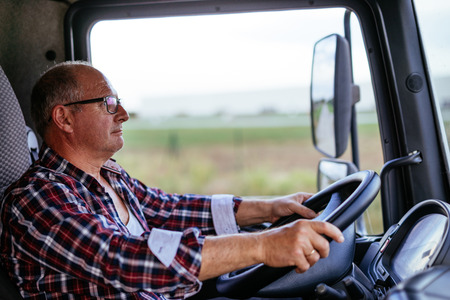 Senior truck driver holding a wheel and driving.