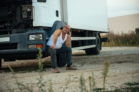calling for help: Senior truck driver calling for help on a mobile phone.