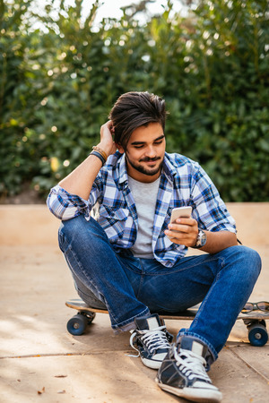 Handsome teenager using a cell phone while sitting on a longboard.